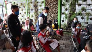 Ketua DPRD Kota Bandung Tedy Rusmawan, AT., M.M., membagikan masker dalam pelaksanaan vaksinasi remaja dan umum, di Kantor KecamatanBandung Kidul, Kamis (14/10/2021).